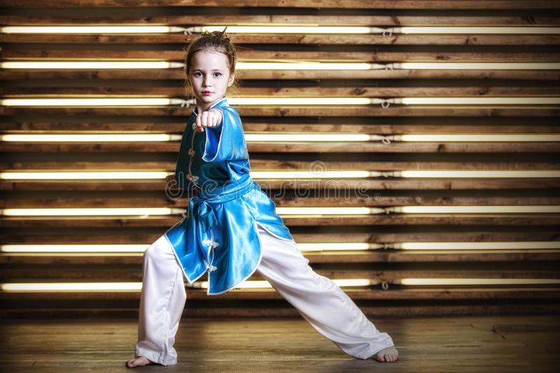 Pretty little girl in the room in sportswear for martial arts is. Wushu or kung fu royalty free stock photo