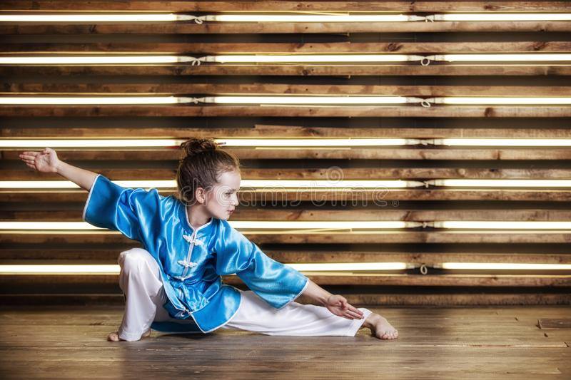 Pretty little girl in the room in sportswear for martial arts is. Wushu or kung fu royalty free stock photography