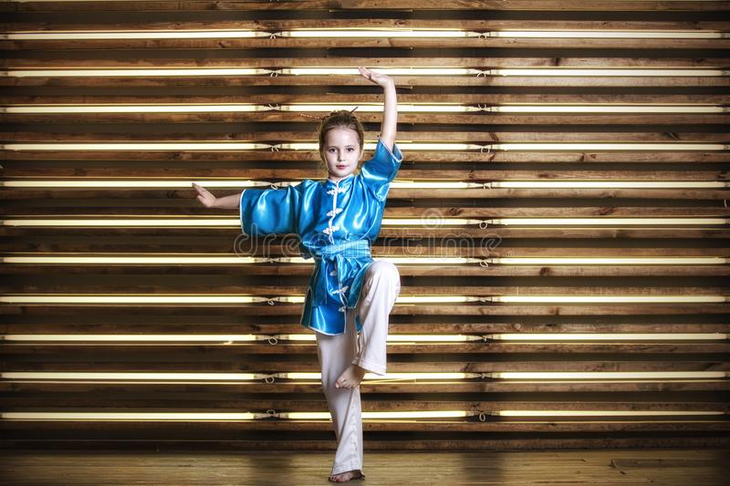 Pretty little girl in the room in sportswear for martial arts is. Wushu or kung fu stock photos