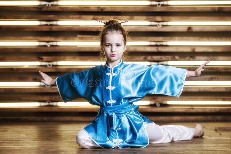 Pretty little girl in the room in sportswear for martial arts is. Wushu or kung fu stock image