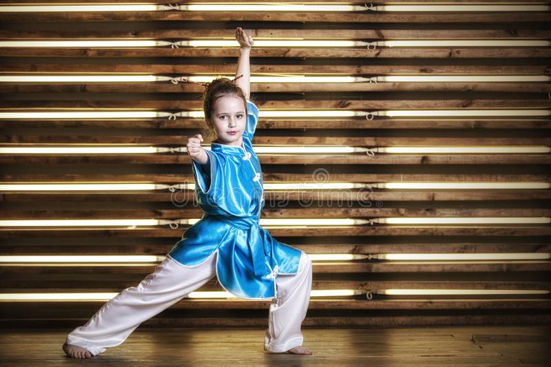 Pretty little girl in the room in sportswear for martial arts is. Wushu or kung fu royalty free stock images