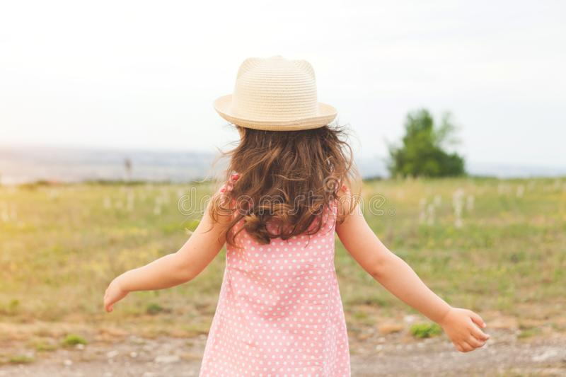 Little girl`s back in hat and dress in summer field royalty free stock image