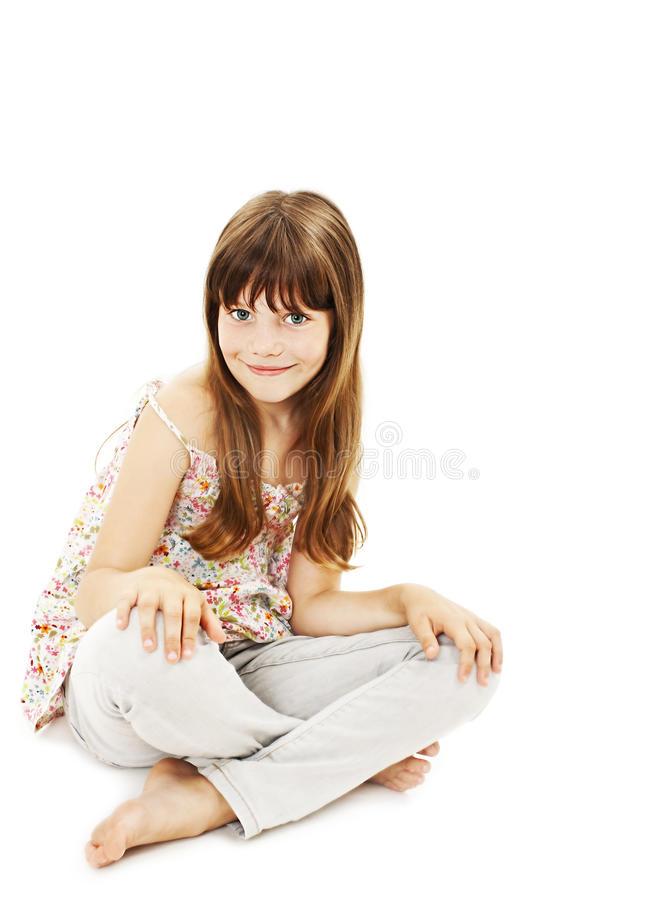 Pretty little girl sitting on the floor in jeans royalty free stock images