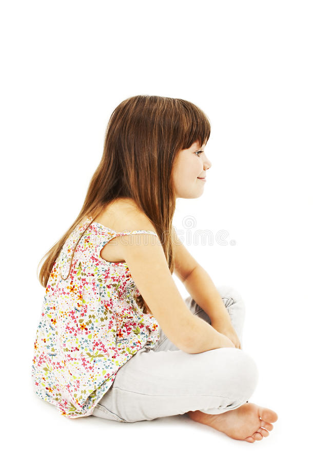 Pretty little girl sitting on the floor in jeans, profile stock photo