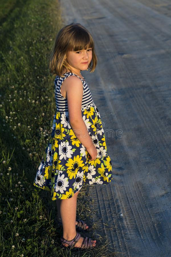 Pretty little girl in summer dress standing with a sad expression royalty free stock photography