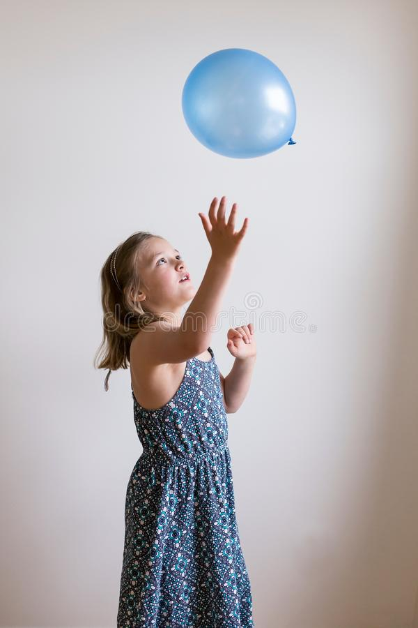 Pretty little girl in summer dress throwing balloon royalty free stock photography