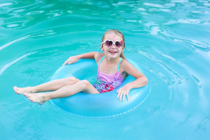 Pretty little girl swimming in outdoor pool and have a fun with inflatable circle stock image