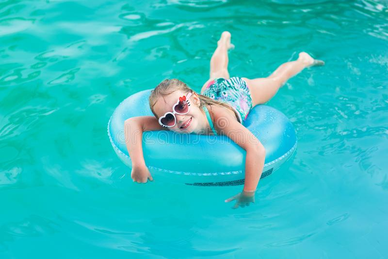 Pretty little girl swimming in outdoor pool and have a fun with inflatable circle royalty free stock image