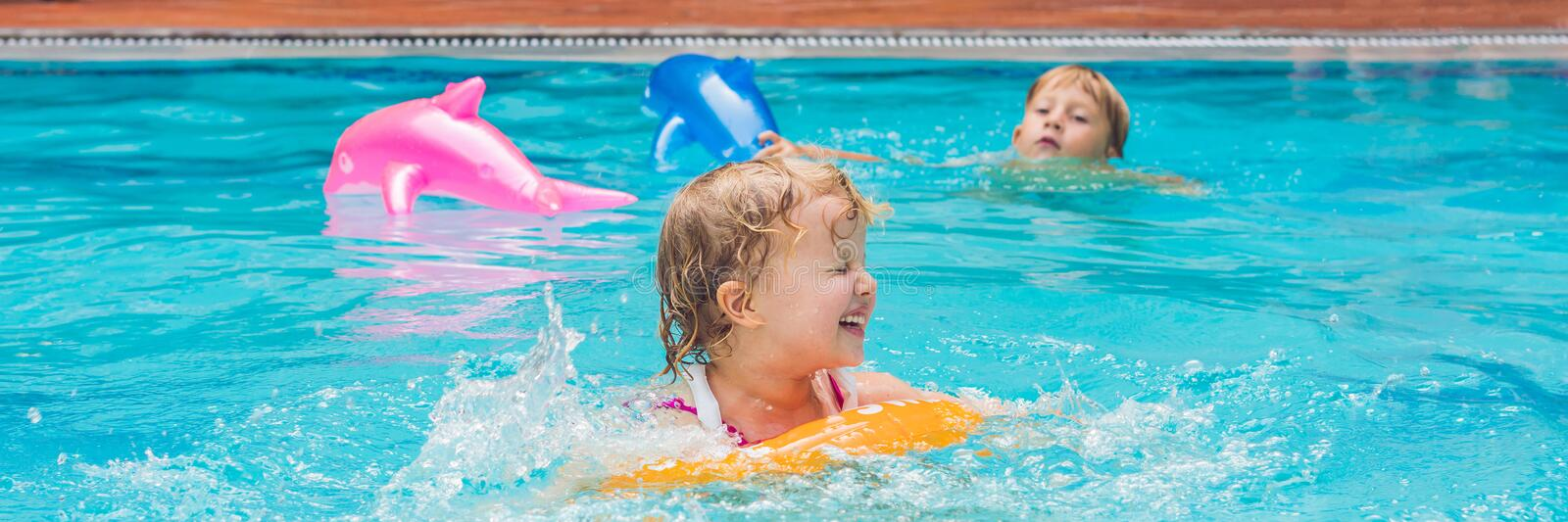 Pretty little girl swimming in outdoor pool and have a fun with inflatable circle BANNER, long format royalty free stock photo