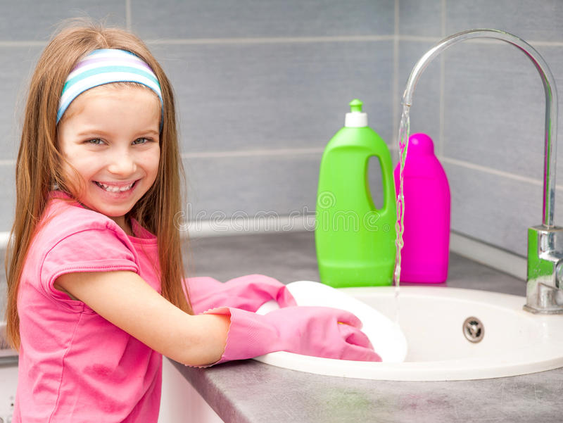 Little girl washing the dishes stock images