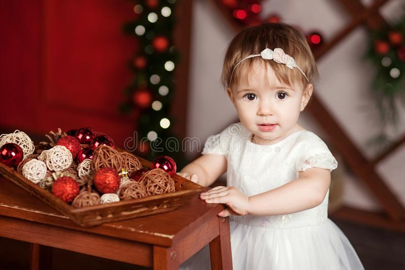 Pretty little girl in white dress playing and being happy about christmas tree and lights. Winter holidays.New Year and Christmas stock images