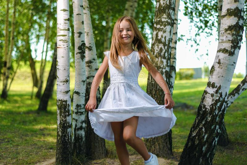 Pretty little girl in white dress whirls and dances among the trees royalty free stock images