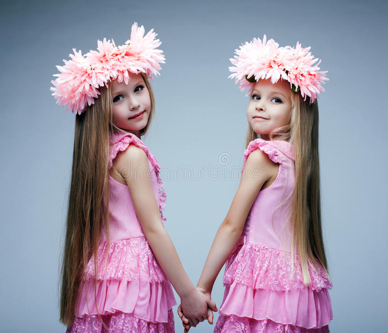 Pretty little girls in pink dresses. Glamour portrait of little girls in pink dresses royalty free stock images