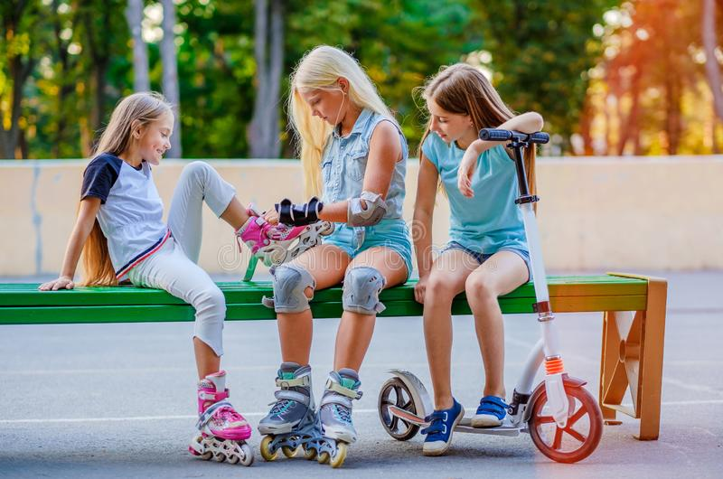 Little girls putting on rollerskates stock images