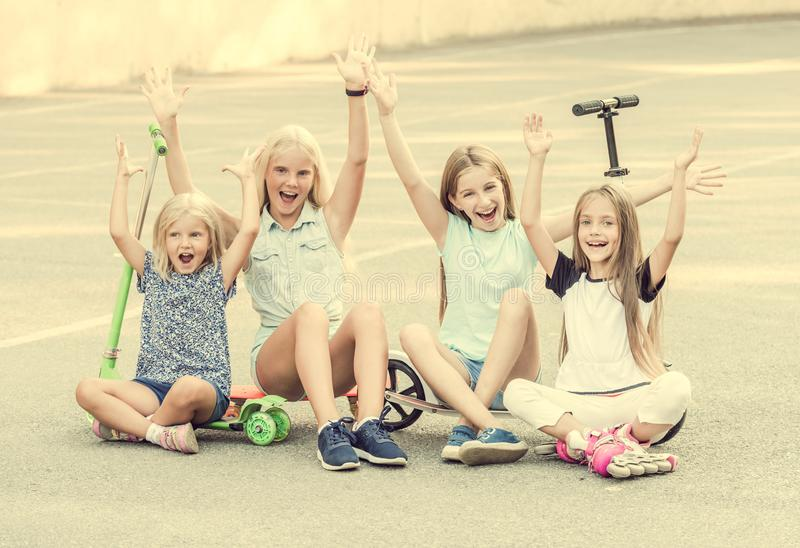 Little girls smiling sitting on the ground with raised hands royalty free stock image