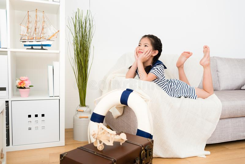 Pretty little kid girl lying down on sofa couch. Beautiful pretty little kid girl lying down on sofa couch daydreaming and thinking adventure travel plan when stock images