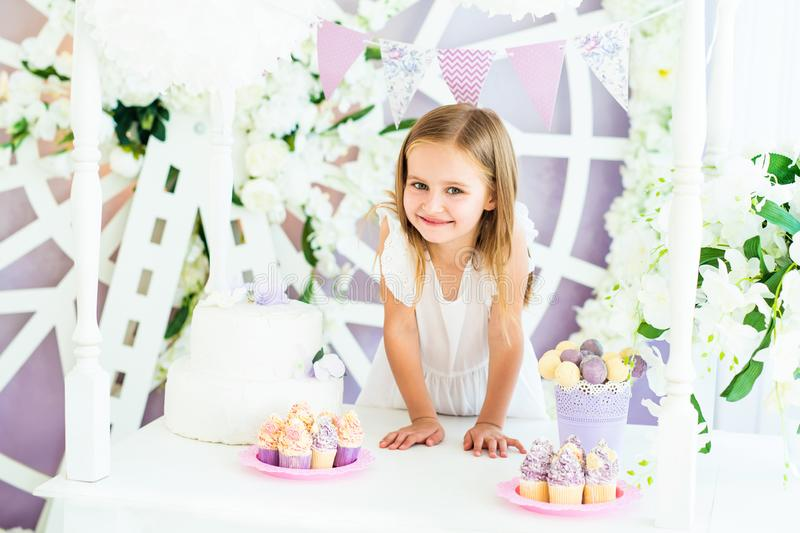 Pretty smiling little girl in the candy bar stock photos