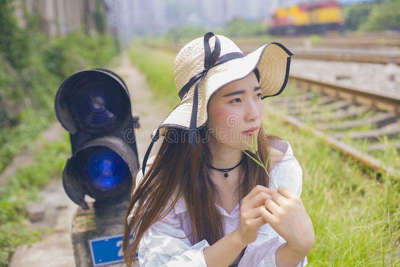 Pure and lovely Asian girl. Pretty lovely girl and rail background. A slightly retro portrait. Play on the rails. Portrait close-ups of Asian faces royalty free stock images