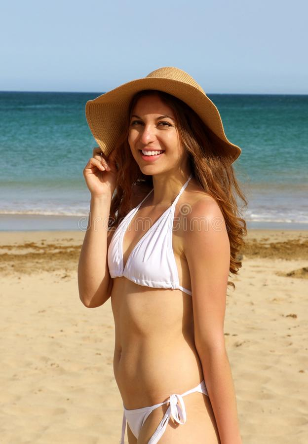 Pretty lovely girl with straw hat and white bikini happy on the beach. Cheerful young adult model looking at the camera on Canary royalty free stock images