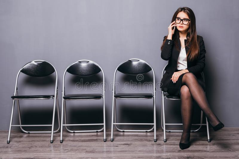 Pretty lovely manager lady using mobile phone calling and sitting on wood floor chair in gray wall background room waiting for int stock image