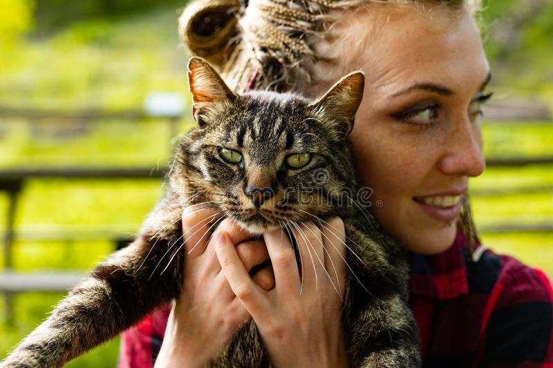 Pretty loving young woman hugging her cat. To her chest looking aside with a smile in a close up outdoor portrait royalty free stock image