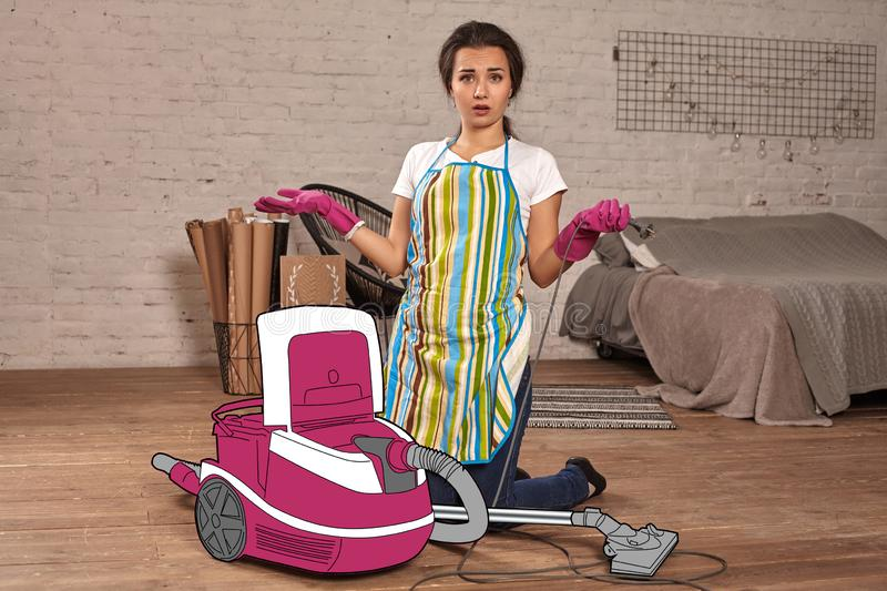 Girl in an apron, rubber gloves and red lips has opened the lid of the cartoon vacuum cleaner and looking confused. stock photography