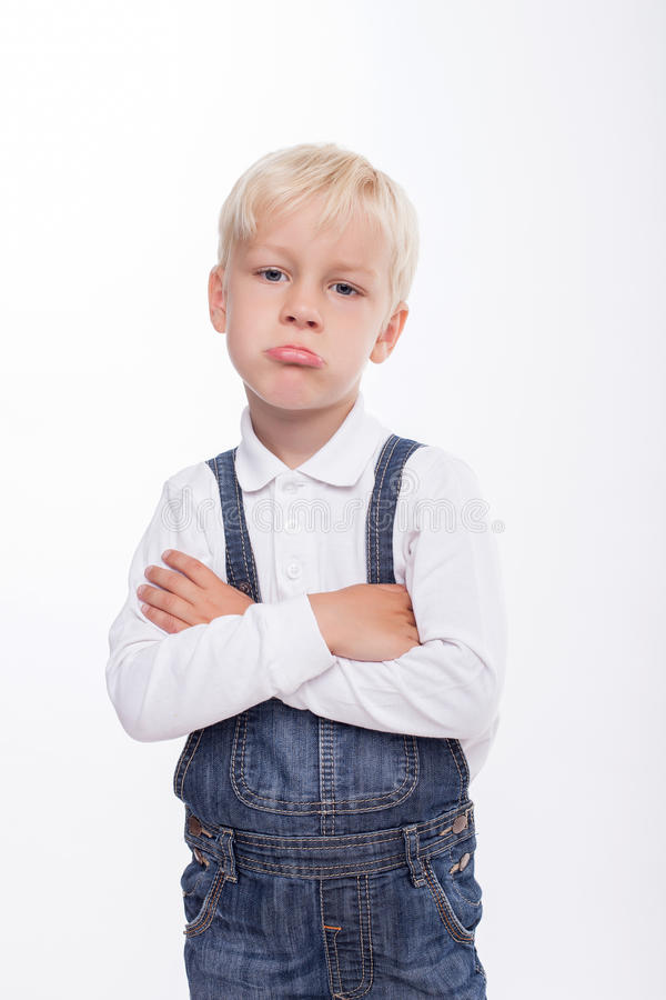 Pretty male blond child is feeling grievance. Cheerful boy is resentful. He is looking forward with insult. The boy crossed his hands and pouts. Isolated on stock photo