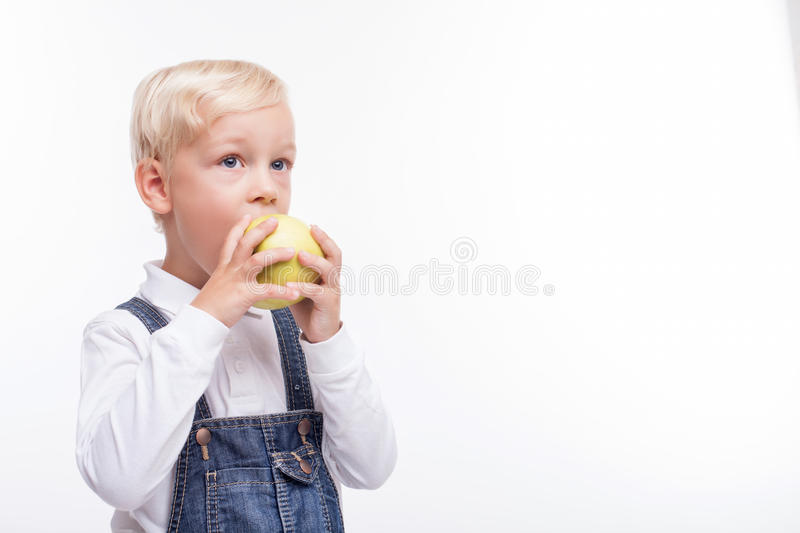 Pretty male child is eating green fruit. Cheerful blond boy is biting a healthy apple with appetite. He is standing and looking forward with joy. Isolated and stock photo