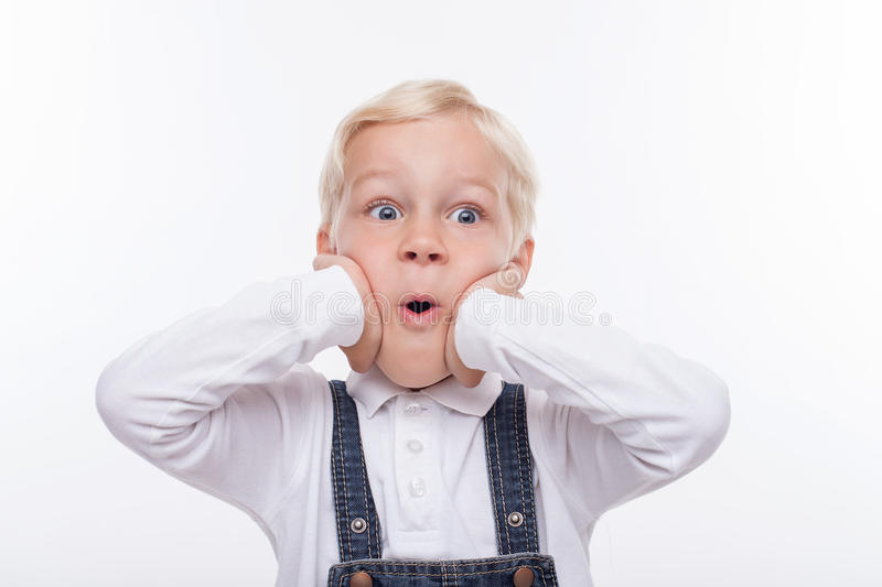 Pretty male child is expressing his surprise. Cute small boy is looking forward with shock. He is standing and touching his face with amazement. His mouth is royalty free stock photos