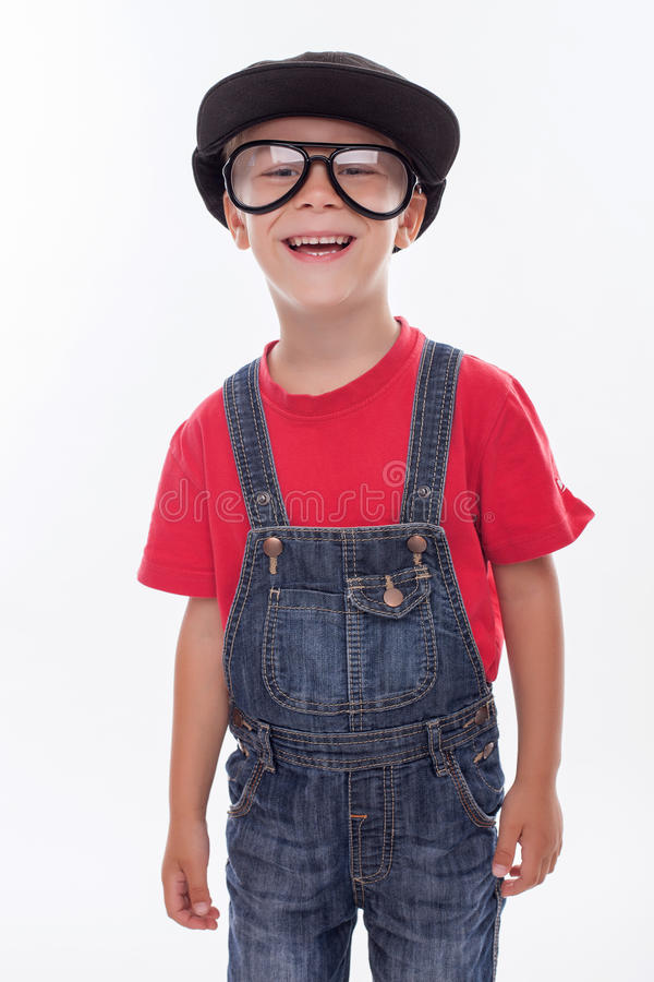 Pretty male child is making fun with strange cap. Cute boy is standing in funny hat and huge eyeglasses. He is looking forward and laughing. Isolated on royalty free stock image