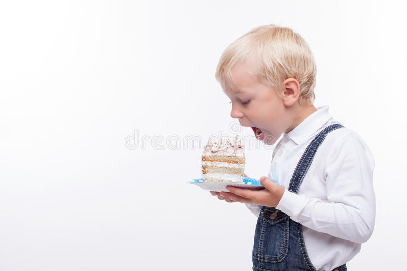 Pretty male child is tasting sweet food. Cheerful boy is eating a cake with enjoyment. He is holding a plate and opening his mouth widely. The boy is looking at stock image