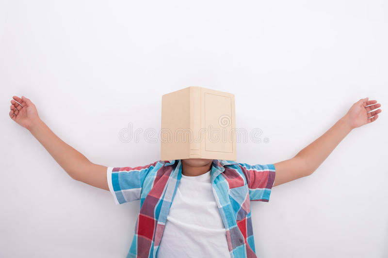 Pretty male teenager is tired of studying. Cute boy is lying on floor and sleeping. He is exhausted of learning. The book is situated on his face. Isolated on royalty free stock photos
