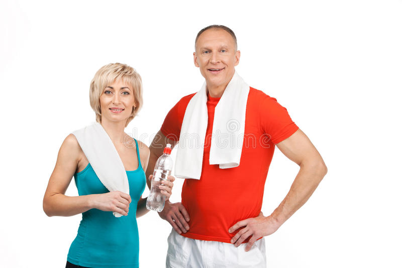 Pretty man and woman standing in gym. royalty free stock image