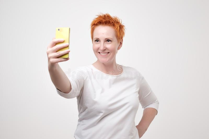 Pretty mature happy woman with red hair making selfie on smartphone stock photos