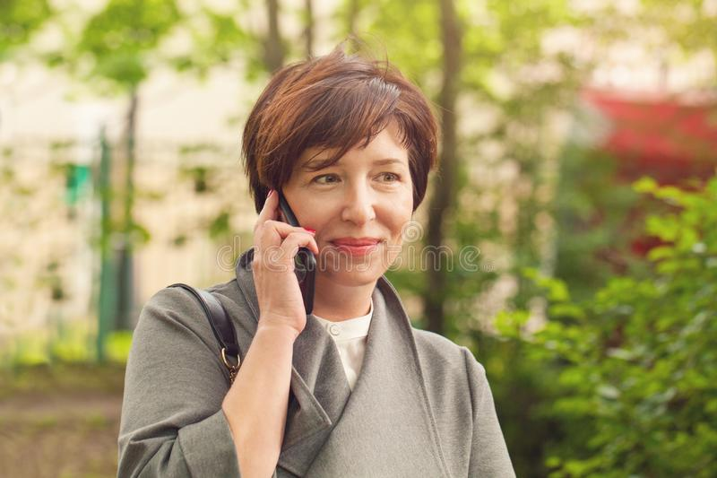 Pretty mature woman phone, outdoors portrait royalty free stock image