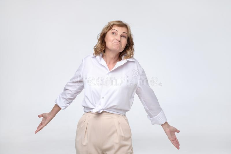 Pretty mature woman retired boss looking confused shrugs her shoulders. royalty free stock image