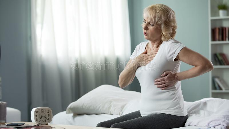 Pretty mature woman sitting on bed and suffering from heart attack, health royalty free stock photography