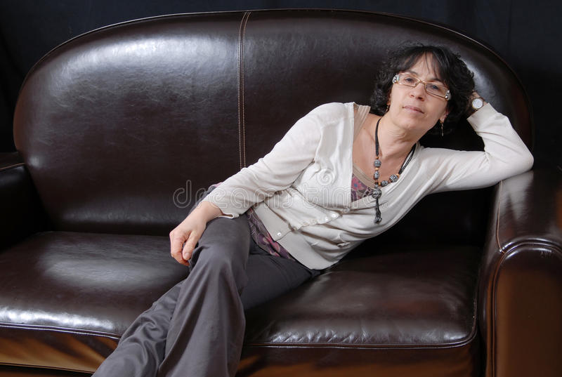 Pretty mature woman sitting on a sofa stock photography