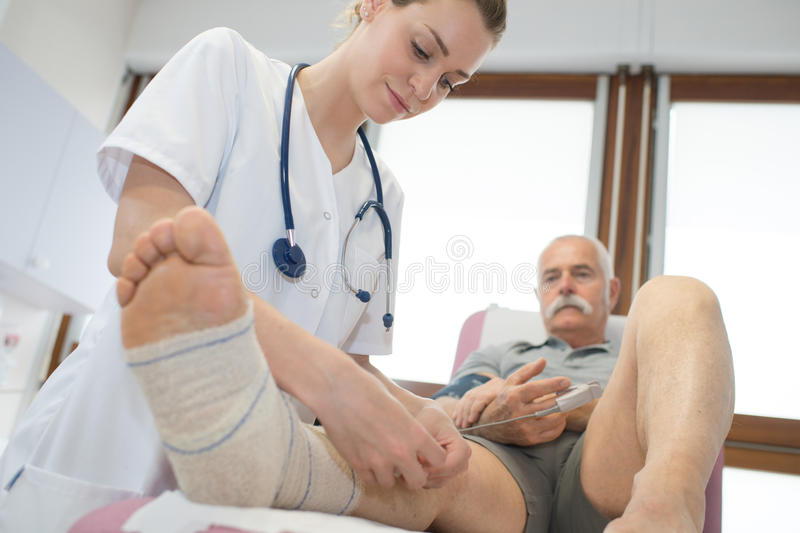 Pretty medical doctor bandaging elder mans broken leg royalty free stock photography