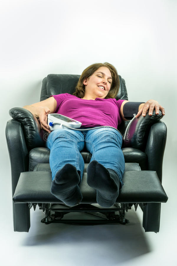 Pretty middle-age woman laying in black leather recliner armchair. Checking blood pressure using portable blood pressure machine. stock photography