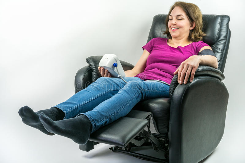 Pretty middle-age woman sitting in black leather recliner armchair. Checking blood pressure using portable blood pressure machine. stock photography