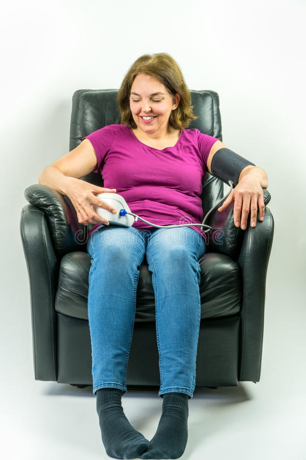 Pretty middle-age woman sitting up right in black leather recliner armchair. Checking blood pressure using portable blood pressure stock image