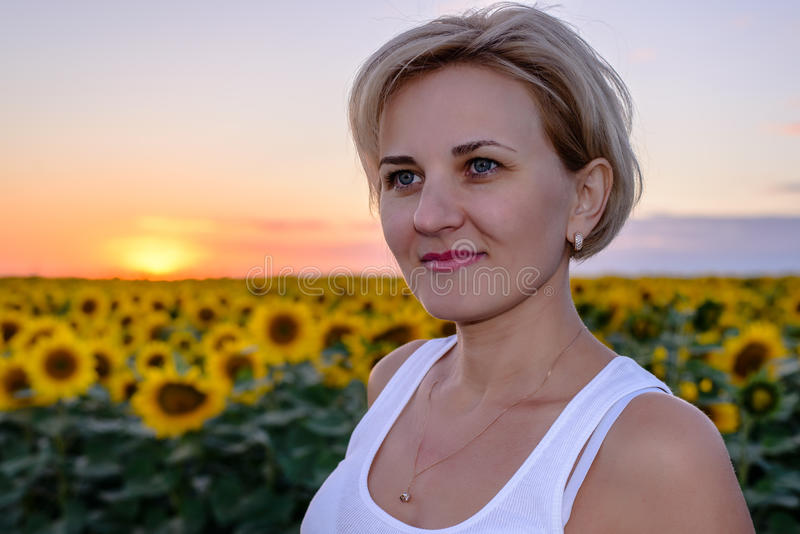 Pretty middle-aged blond woman in the country. Pretty middle-aged blond woman country standing looking side of the camera against colorful sunset field of yellow stock images