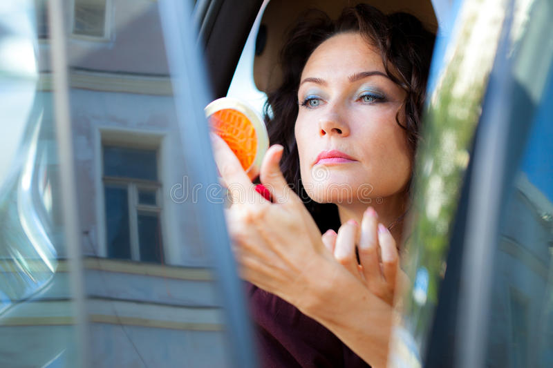Pretty middle-aged woman checked the makeup royalty free stock photography