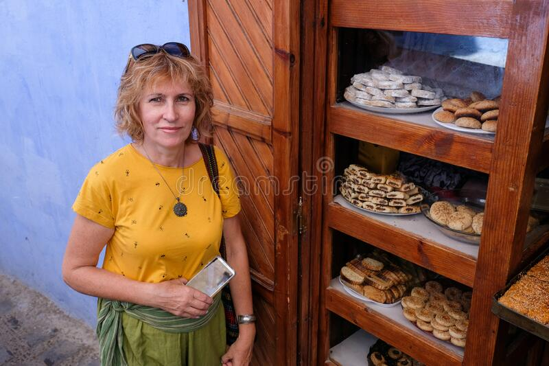 Pretty middle-aged woman near cakes sale in blue city of  Chefchaouen,Morocco stock photos