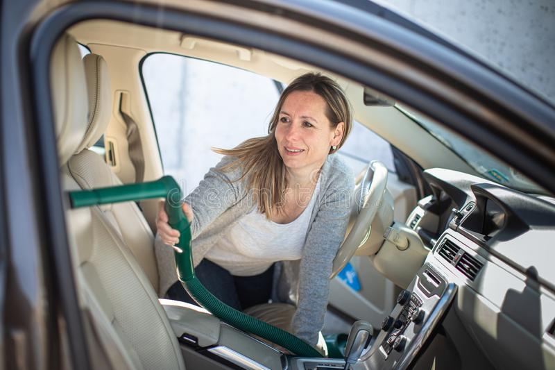 Pretty, middle aged woman vacuum cleaning the interior royalty free stock image