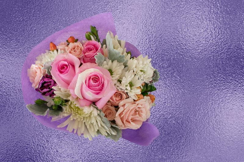 Pretty miniature bouquet with pink roses on purple foil background stock image
