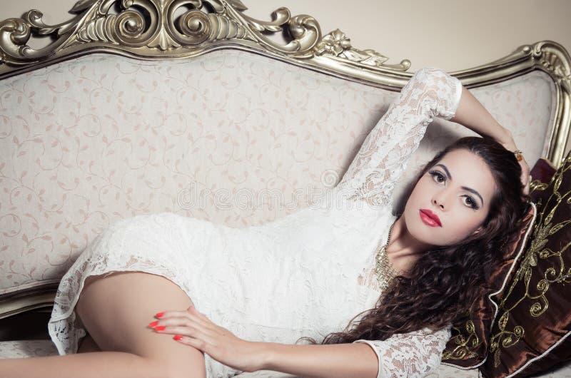 Pretty model girl sitting on victorian sofa posing stock image