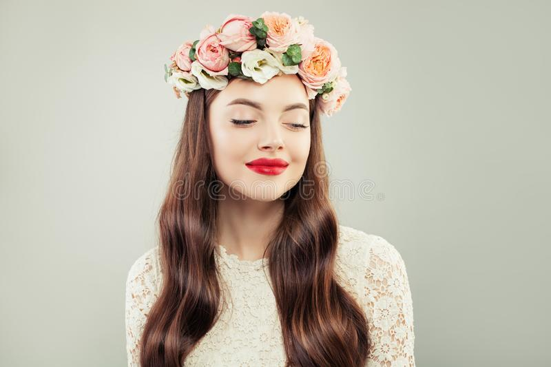 Pretty Model Looking Aside. Beautiful Woman with Long Hair, Make up and Flowers. Spring Beauty Girl.  royalty free stock photo