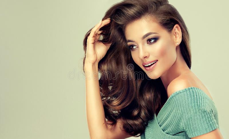 Pretty model is touching softly curls of own hair. Hair care and beauty products. stock images